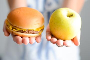 Mains présentant d'un coté un burger et de l'autre une pomme